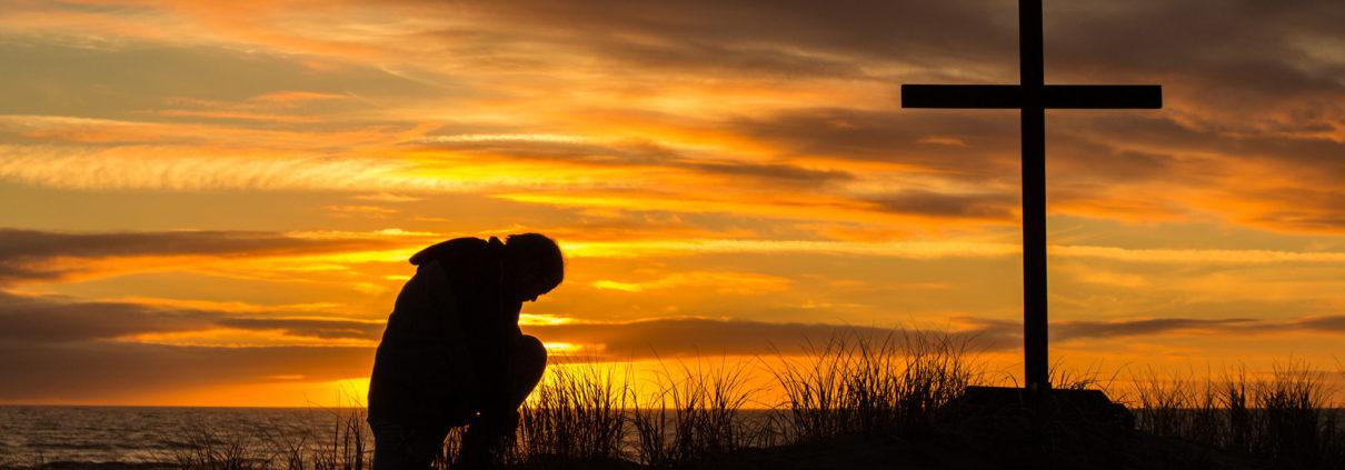 Man praying in front of cross at sunset